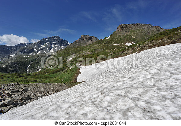 Snow in the summer under the mountains - csp12031044