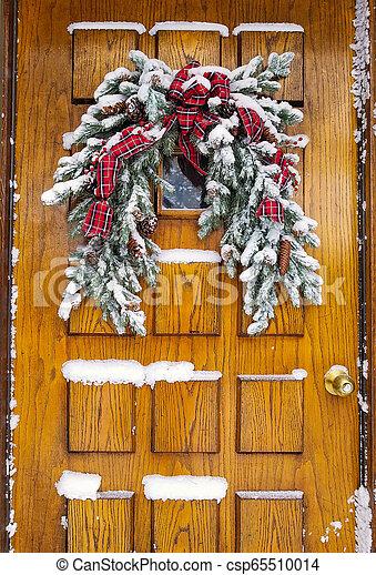 snow on Christmas pine bough on door - csp65510014