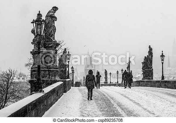 Snow storm on Charles Bridge in Prague - csp89235708