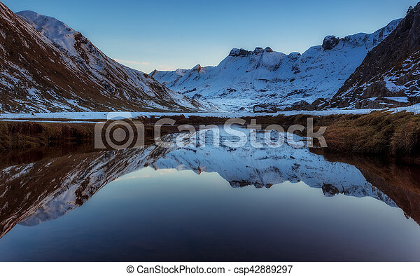 Snowed mountain reflection in the river - csp42889297