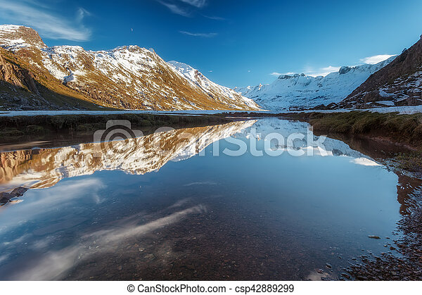 Snowed mountain reflection in the river - csp42889299