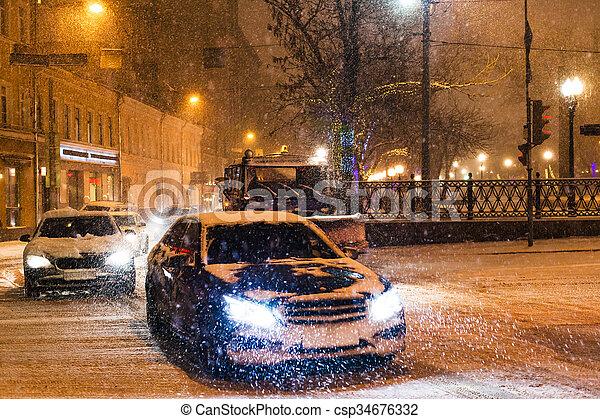 snowfall in night city - cars traffic under snow - csp34676332