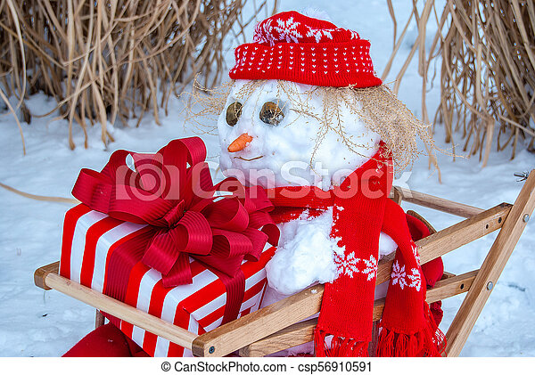 snowman in sled with holiday gift - csp56910591
