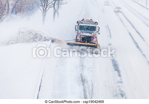 Snowplow removing the Snow from the Highway during a Snowstorm - csp19042469