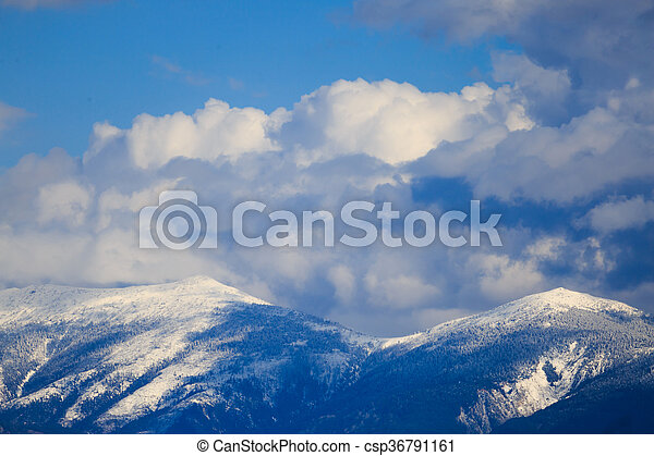 Snowy mountain range with blue sky and clouds. - csp36791161