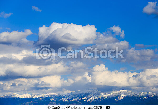 Snowy mountain range with blue sky and clouds. - csp36791163