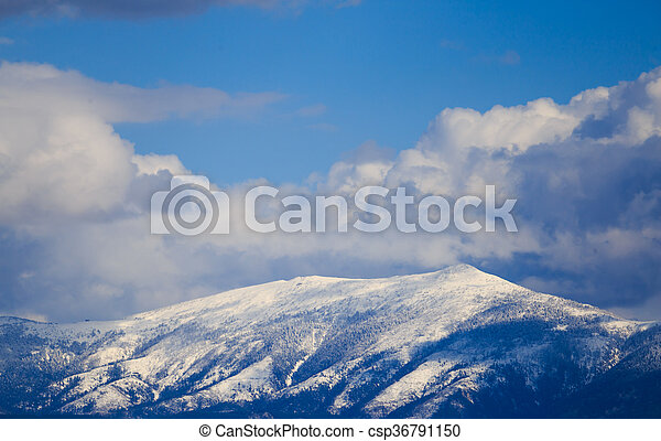 Snowy mountain range with blue sky and clouds. - csp36791150
