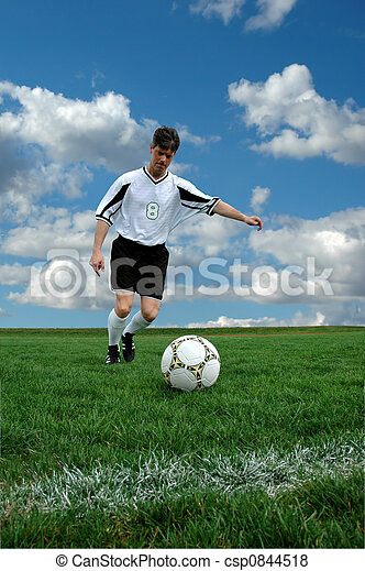 Soccer player in action shot kicking a ball against a colorful sky