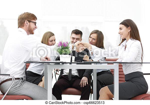 Un apretón de manos de socios en un escritorio en la oficina - csp66623513