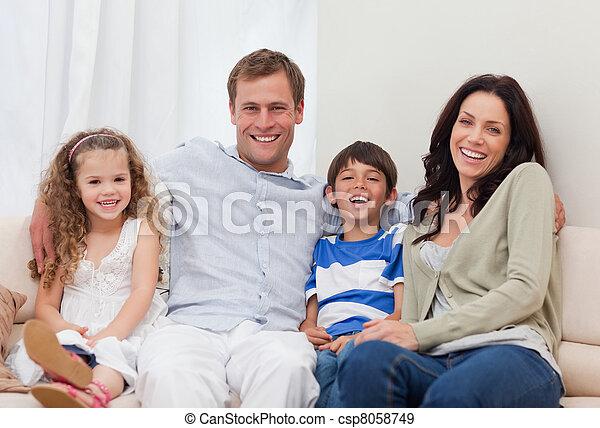 Familia sentada en el sofá juntos - csp8058749