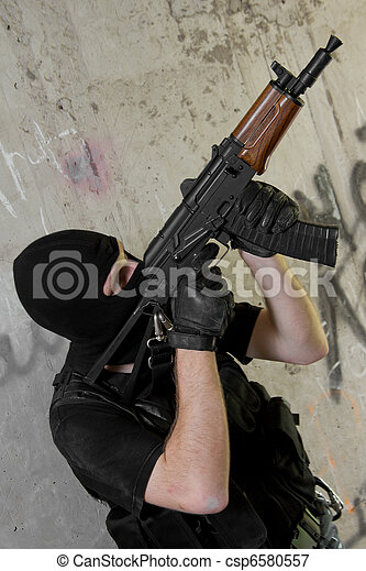 Soldier in black mask moving upstairs with AK-47 rifle - csp6580557