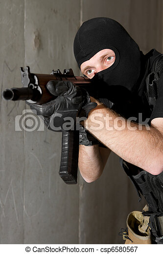Soldier in black mask targeting with AK-47 rifle - csp6580567