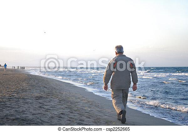 Un hombre mayor solitario caminando por la playa - csp2252665