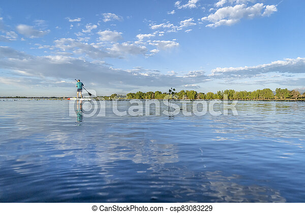 solo stand up paddler on a calm lake in Colorado - csp83083229