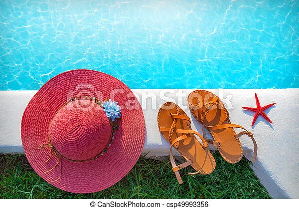 Sombrero y zapatos junto a la piscina - csp49993356