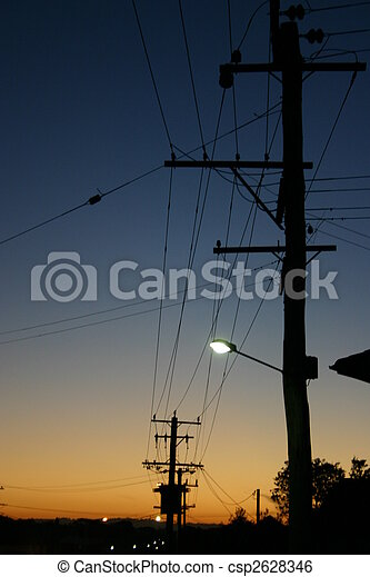 Some distribution powerlines silouetted at sunset. - csp2628346