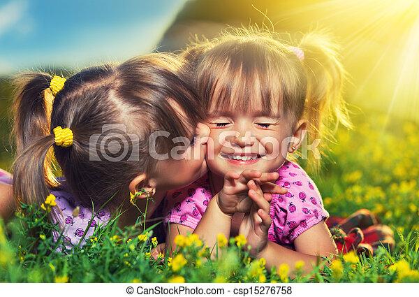 Glückliche Familie. Kleine Zwillingsschwestern küssen und lachen im Sommer draußen - csp15276758
