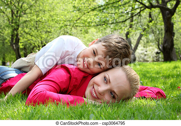 son lies on back of mother lying on grass in park in spring - csp3064795