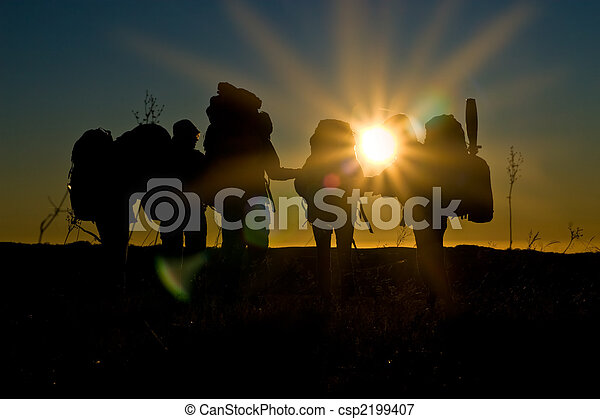 Wanderer gehen im Sonnenuntergang mit Sonnenstrahlen und Reflexionen - csp2199407