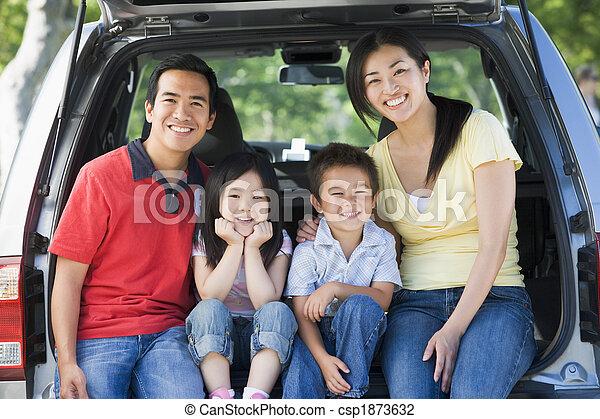 Familia sentada detrás de la camioneta sonriendo - csp1873632