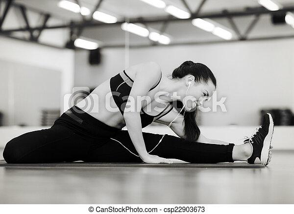 Mujer sonriente estirada en la alfombra en el gimnasio - csp22903673