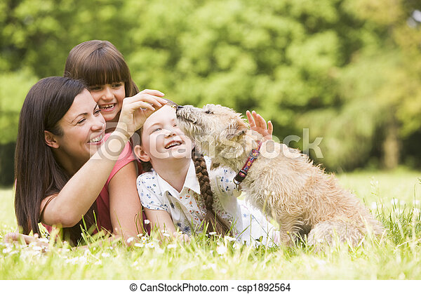 Madre e hijas en el parque con perros sonriendo - csp1892564