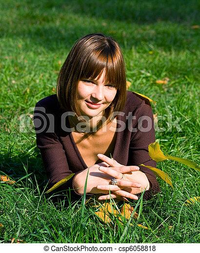 Chica sonriente en un pasto verde - csp6058818