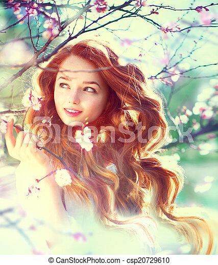 La chica de la belleza de primavera con el pelo largo y rojo al aire libre - csp20729610