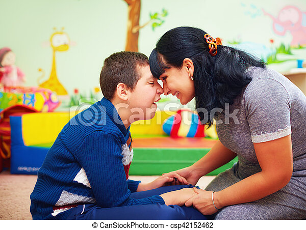 soulful moment. portrait of mother and her beloved son with disability in rehabilitation center - csp42152462
