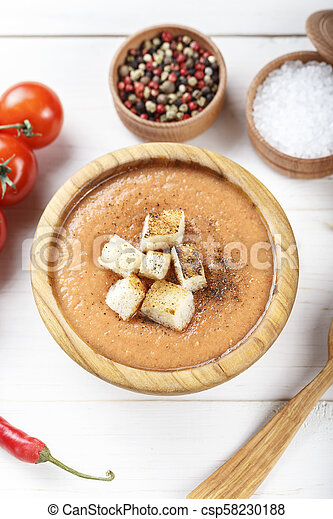 soup gazpacho with crackers, in a wooden plate, on a white wooden background. - csp58230188