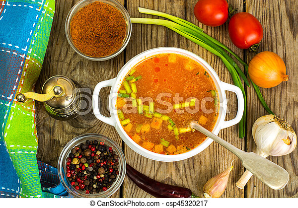 Soup in white bowl on wooden background. - csp45320217