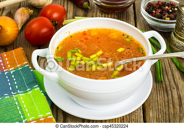 Soup in white bowl on wooden background. - csp45320224