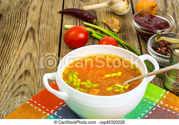 Soup in white bowl on wooden background. - csp45320226