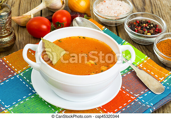 Soup in white bowl on wooden background. - csp45320344