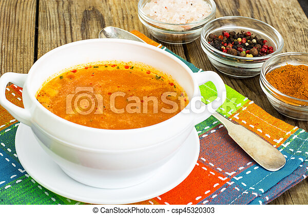 Soup in white bowl on wooden background. - csp45320303
