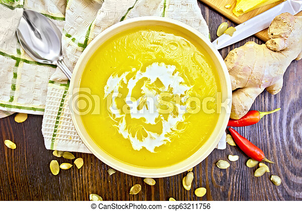 Soup-puree pumpkin with cream in bowl on board top - csp63211756