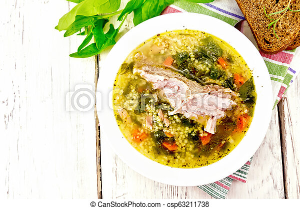 Soup with couscous and spinach in plate on light board top - csp63211738