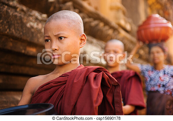 Southeast Asian young Buddhist monks walking morning alms - csp15690178