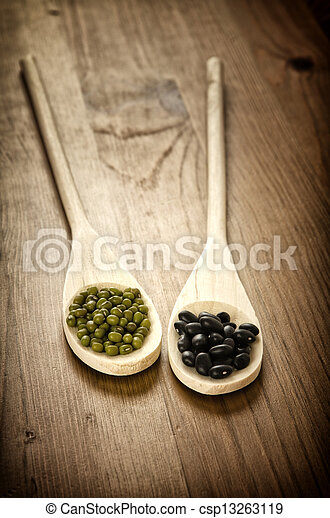 Soybeans and black beans in wooden spoons - csp13263119