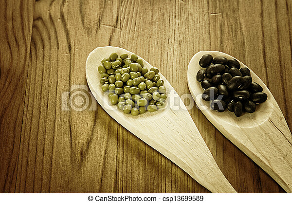 Soybeans and black beans in wooden spoons - csp13699589