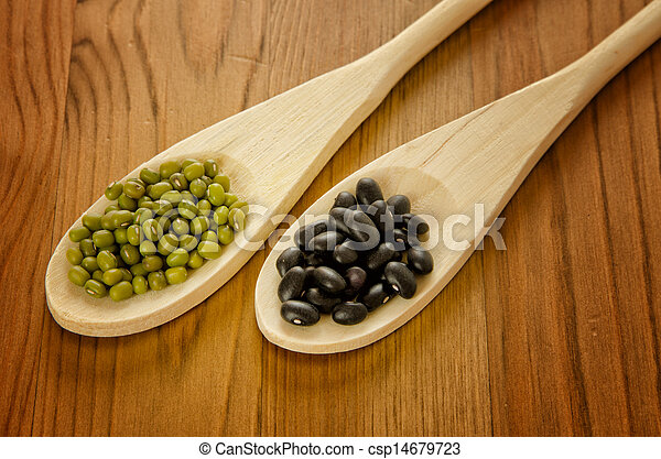 Soybeans and black beans in wooden spoons - csp14679723