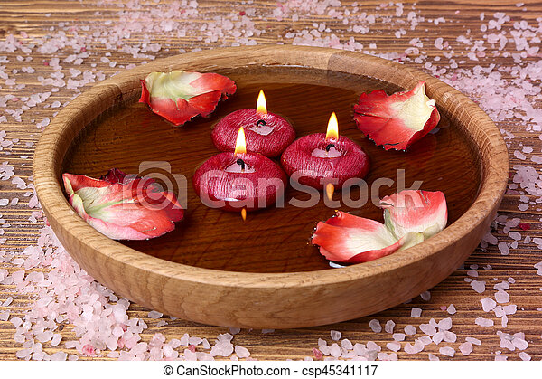 Spa concept with rose petals, salt and candles that float in a wooden bowl  with water