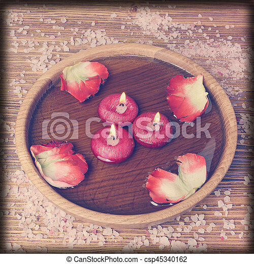 Spa concept with rose petals, salt and burning candles that float in a  water, imitation filter instagram