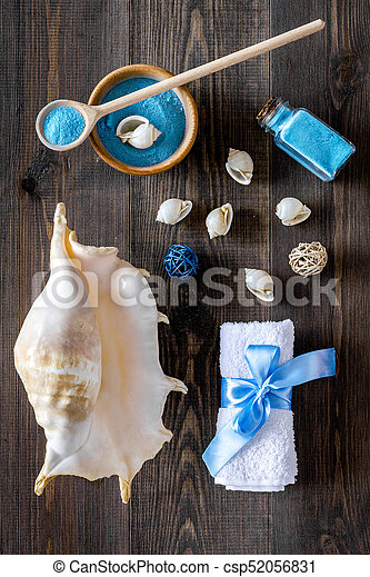 spa set with blue sea cosmetics for bath and shell on wooden desk background top view