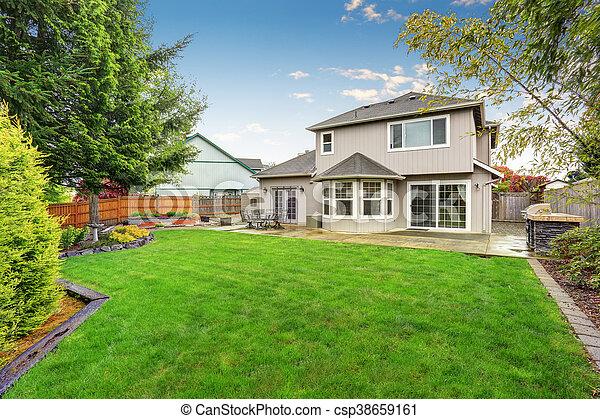 Spacious backyard garden with green lawn and Cozy patio area - csp38659161