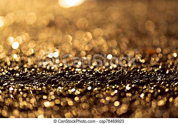 Sparkling light boke blur. Golden glitter particles background. - csp78469923