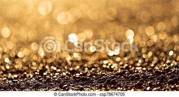 Sparkling light boke blur. Golden glitter particles background. - csp78674705