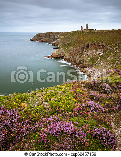 Spectacular cliffs in Cap Frehel with lighthouse on a cloudy day in summer - csp62457159