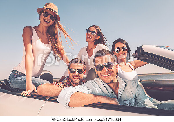 Spending great time together. Group of young happy people enjoying road trip in their white convertible and smiling at camera - csp31718664