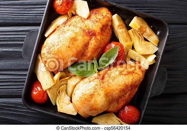 Spicy chicken breast with baked artichokes and tomatoes close-up on a plate. Horizontal top view - csp56420154